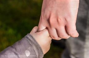 Kinderhand hält Hand eines Erwachsenen