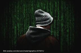 vermummte Person vor Zahlencodes